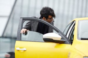 Young Businessman Getting In Taxi